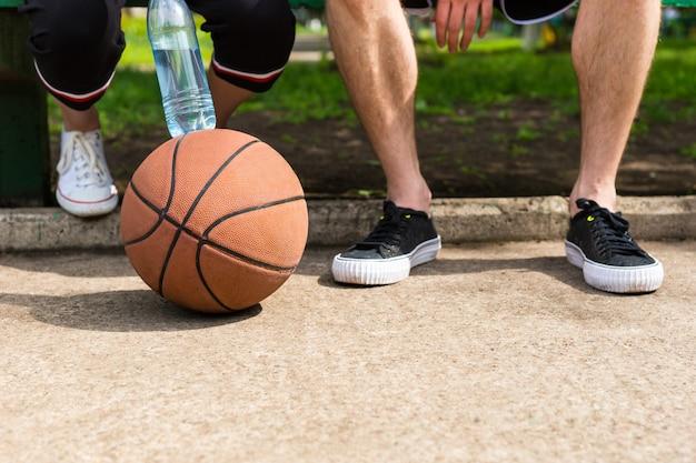 낮은 각도 경기 후 공원 벤치에 앉아 젊은 운동 커플의 발에서 지상에 농구의 보기를 닫습니다
