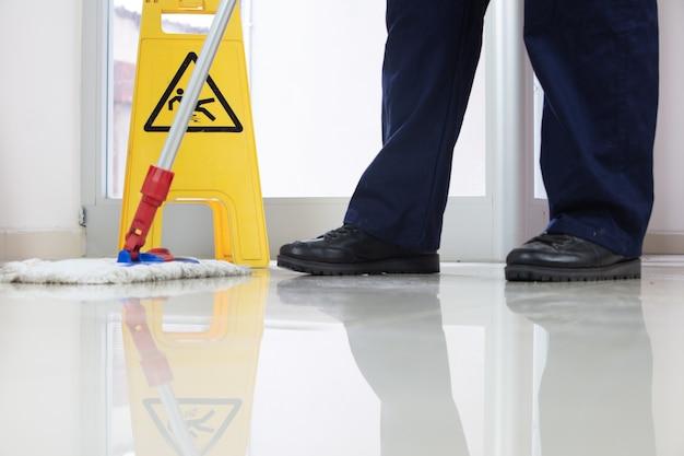 黄色い注意の濡れた床のサインの近くでモップで床を掃除する人のローアングルのクローズアップ