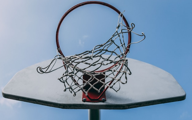 Low angle closeup shot of a basket hoop on a backboard