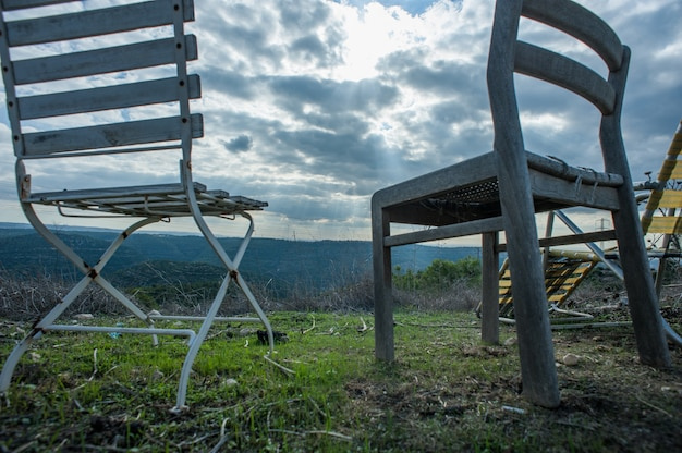 Colpo del primo piano di angolo basso delle sedie fuori sotto il cielo nuvoloso scuro