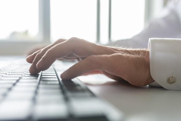 백그라운드에서 밝은 사무실 창 컴퓨터 키보드에 입력하는 사업가의 낮은 각도 근접 촬영보기.