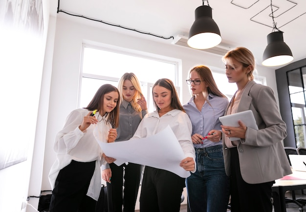 Low angle corporate women checking plans