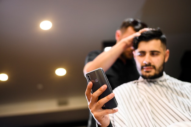 Low angle costumer at barber shop looking at phone with copy space