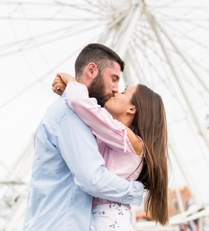 Low angle of couple kissing in front of big wheel