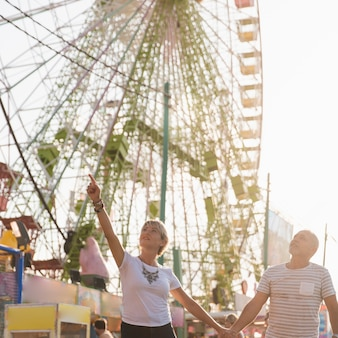 Low angle couple with ferris wheel