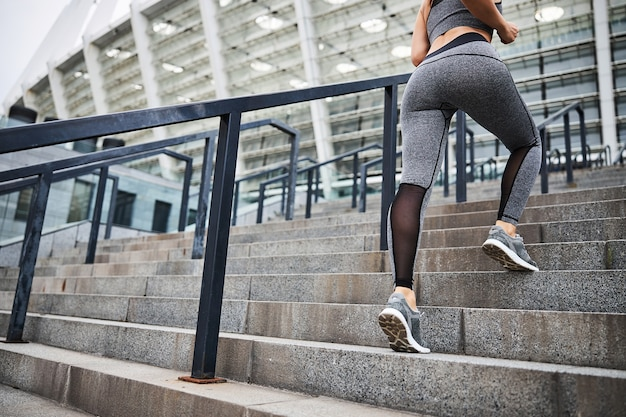Low angle cropped head of athletic female in trainers and sportwear running upstairs to stadium