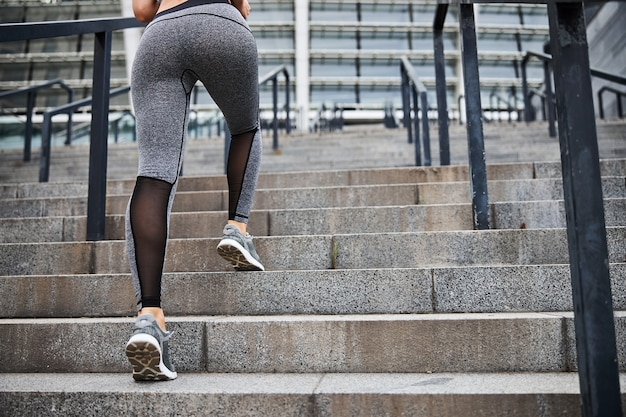 Low angle cropped head of woman in sport legging rushing upstairs for doing sport in city centre