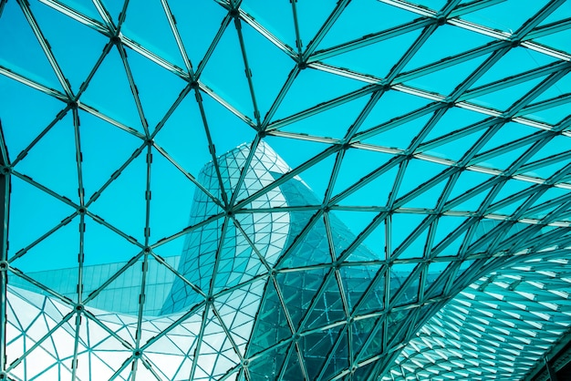 Low angle of curved glass roof with geometric shapes of modern building designed in futuristic style