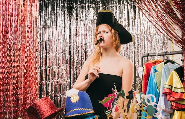 Giovane femmina mascherata di angolo basso per il partito
