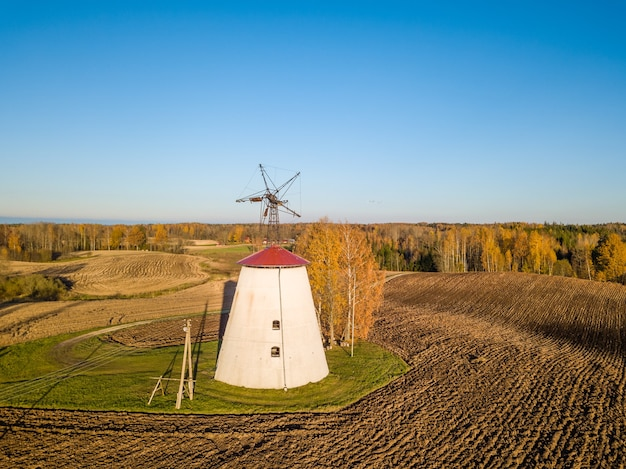 Low angle drone photo of old and abandoned windmill with orange birch tree next to it and blue sky