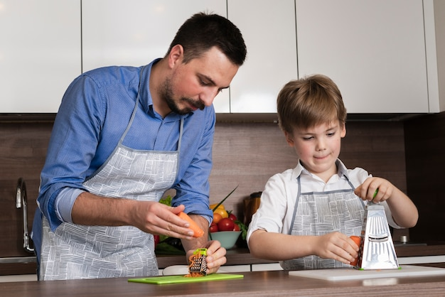 Low angle father and son cooking at home