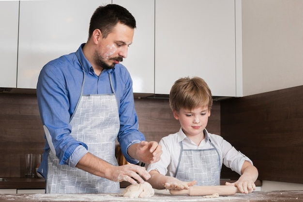 Low angle father and son rolling dough