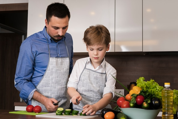 Low angle father teaching son to cut vegetables