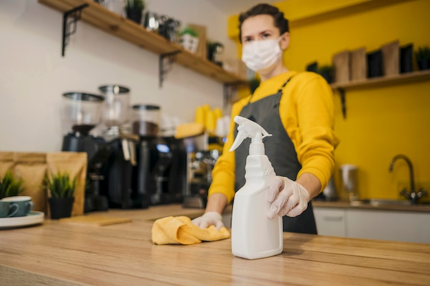 Low angle of female barista with medical mask