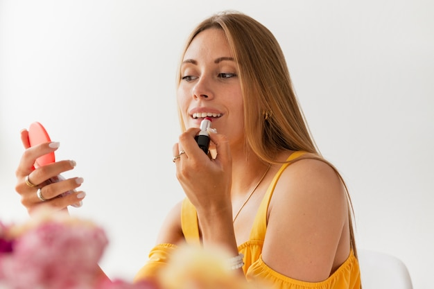Низкий угол женский блоггер, надевая блеск для губ