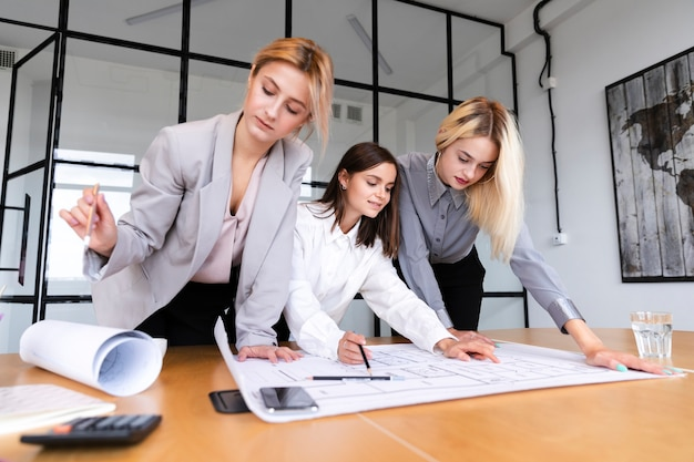 Low angle female employees sketching strategy
