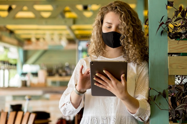 Low angle female with mask using tablet
