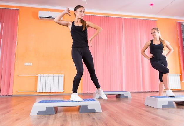 カラフルなダンススタジオのステップエアロビクスクラスで一緒に運動している若い女性のペアのローアングル正面図-スタジオで学生を教えるステップインストラクター