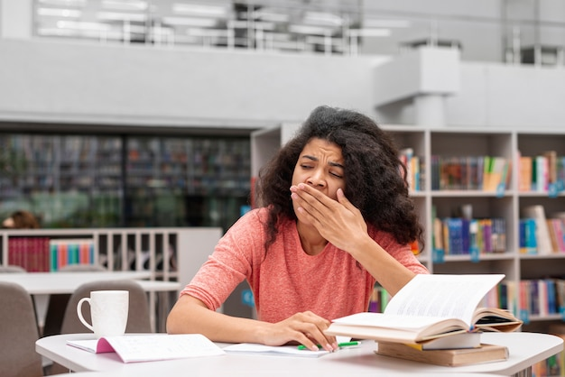 Low angle girl feeling sleepy at library