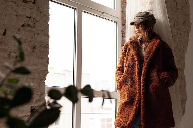 Низкий угол девушка с теплым пальто и шляпой