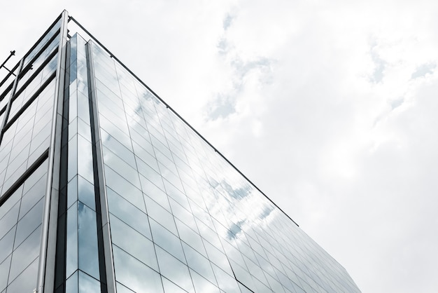 Low angle glass building with clouds