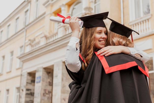 Низкий угол дипломированных девушек
