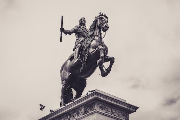 마드리드 왕궁 앞 동상의 낮은 각도 회색조 샷