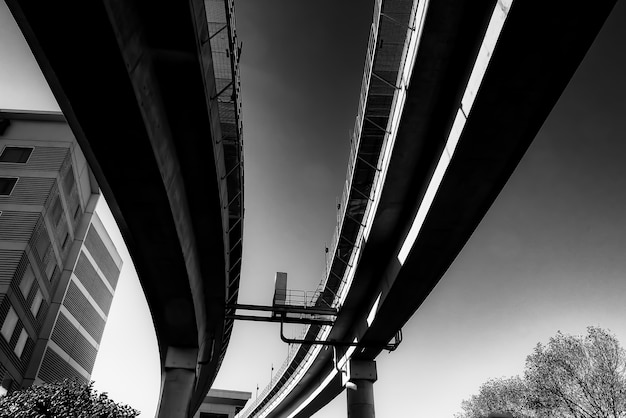 Low angle greyscale of a concrete bridge under the sunlight at daytime