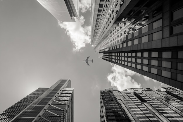 Low angle greyscale shot of an airplane flying above high rise buildings