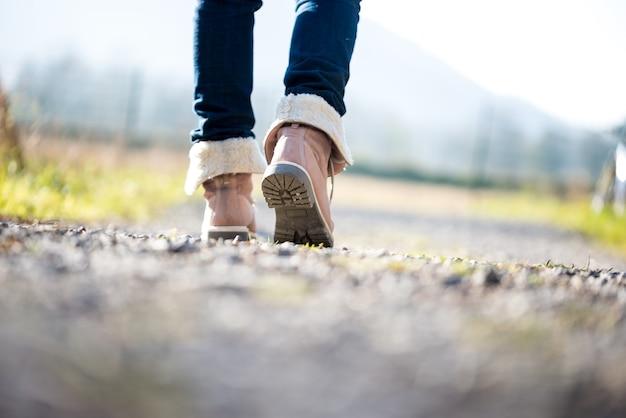 Низкий угол обзора с уровня земли с неглубокой глубиной резкости ног женщины в джинсах и кожаных сапогах до щиколотки, идущей по сельской дороге вдали от камеры.