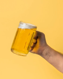 Low angle hand holding pint with beer