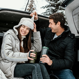 Low angle of happy couple having a warm drink in the car's trunk and playing while on a road trip