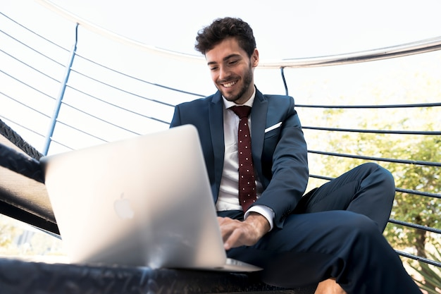 Low angle happy lawyer with his laptop