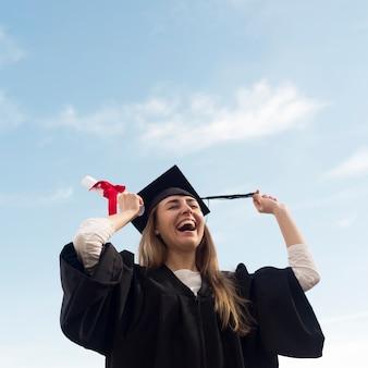 Низкий угол счастливая молодая женщина празднует свой выпускной