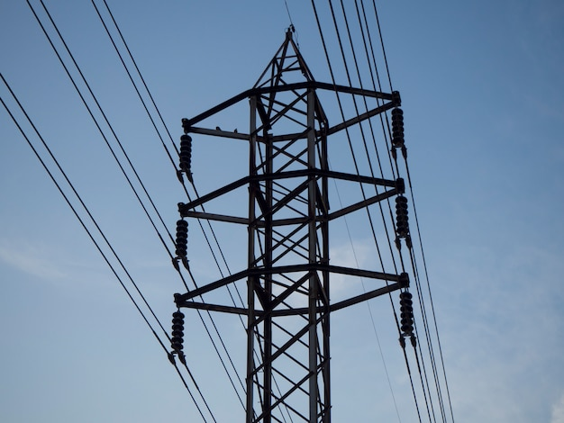 Low angle high voltage electric pole with blue sky