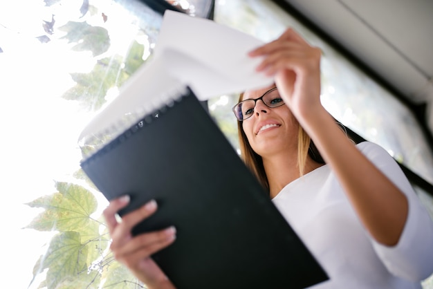 Low angle image of businesswoman looking at documents.