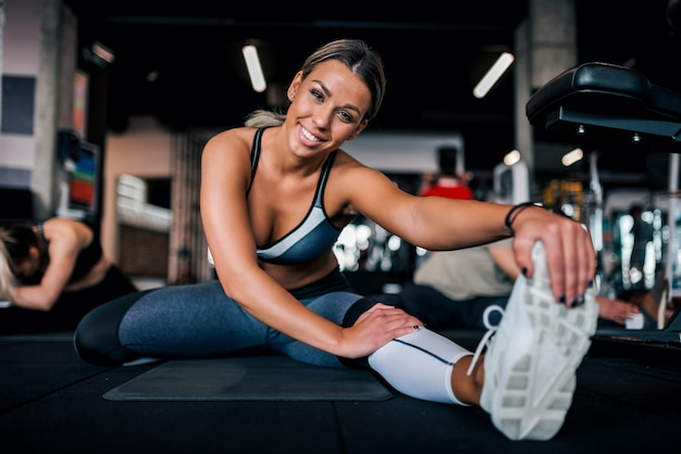 Low angle image of fit woman stretching legs in the gym, smiling at camera.