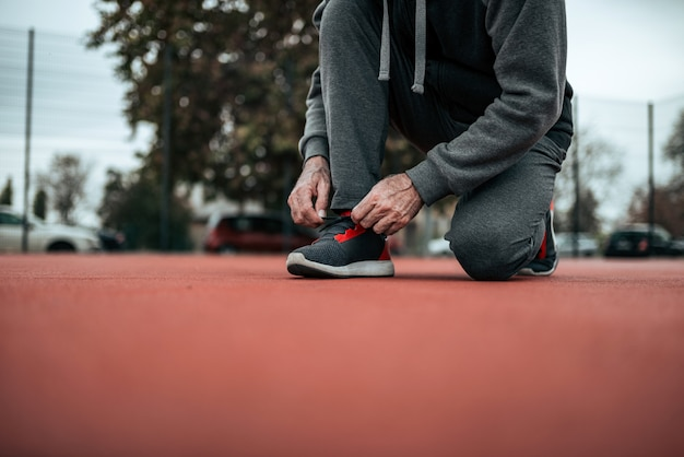 Low angle image of male runner tying shoelaces on tartan track.