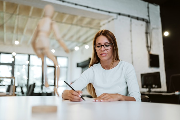 Low angle image of young woman drawing in creative studio.