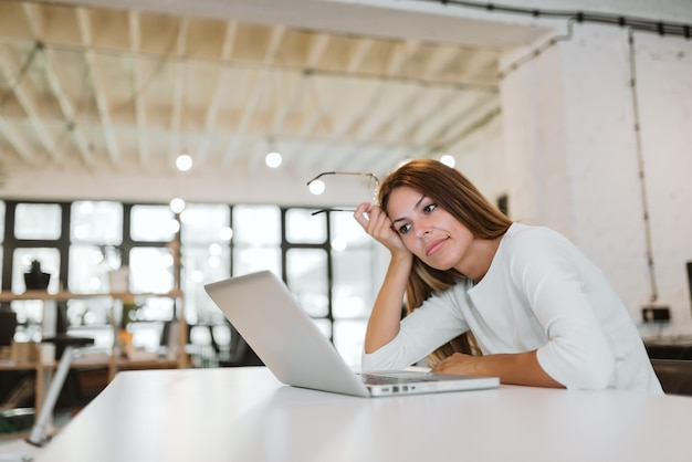 Low angle image of young woman looking at laptop screen in bright office.