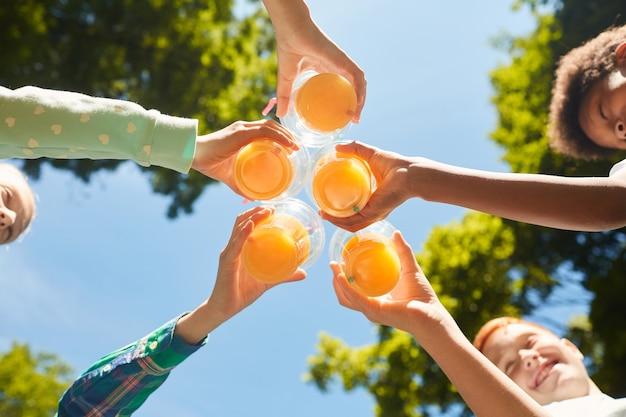 屋外の青い空にオレンジジュースとグラスを保持している低角度の子供たち