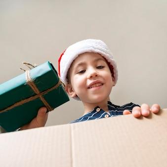 Маленький мальчик с низким углом держит подарок
