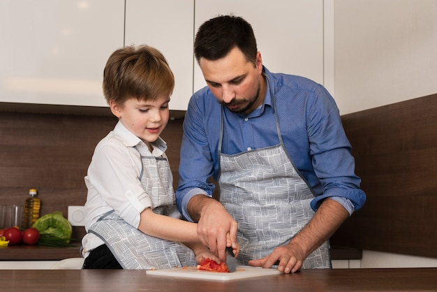 Low angle little boy in kitchen with father