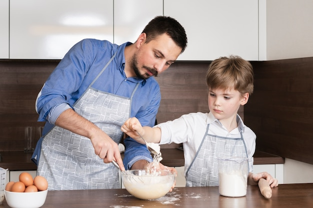 Low angle little son assisting dad in kitchen