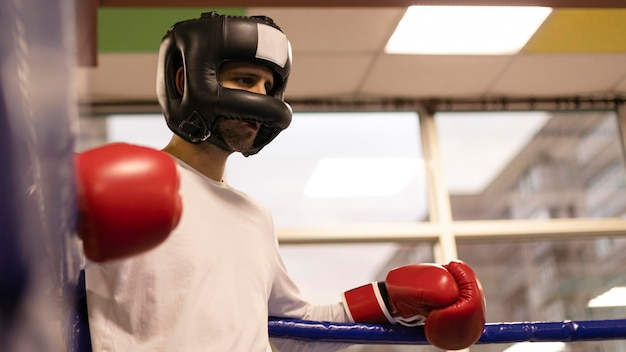 Low angle of male boxer with helmet and gloves