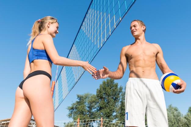 Basso angolo della mano di giocatori di pallavolo maschile e femminile stretta dalla rete