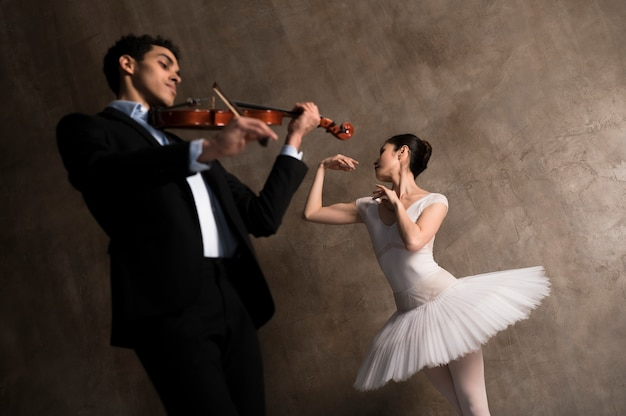 Low angle of male musician and ballerina