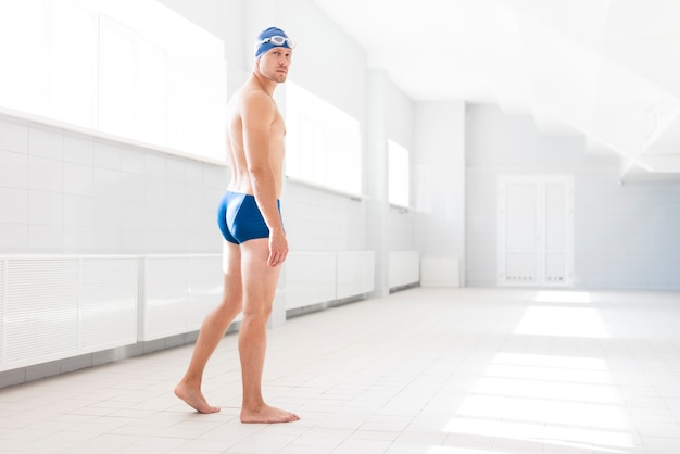 Low angle male swimmer looking behind