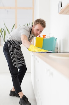 Low angle man cleaning kitchen