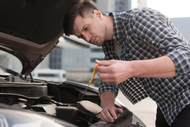 Low angle man fixing car